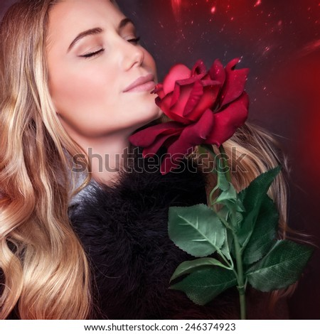 Closeup portrait of beautiful blond woman with closed eyes smelling fresh rose on dark red background, enjoying romantic holiday, happy Valentine day concept - stock photo