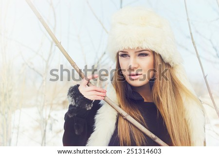 Closeup portrait of beautiful blonde Caucasian young woman with white fur hat and black coat outdoors in winter. Horizontal, retouched, soft tones filter, pastel finish look. - stock photo