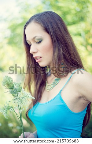 closeup portrait of beautiful brunette young woman having fun relaxing holding field flower on summer green outdoors copy space background - stock photo