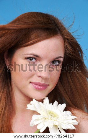 Closeup portrait of beautiful cacuacsian woman with white flower - stock photo