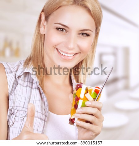 Closeup portrait of beautiful cheerful woman enjoying tasty juice fruits salad, having breakfast at home, healthy eating concept - stock photo