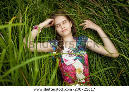 Closeup portrait of beautiful cute girl sleeping in high grass - stock photo