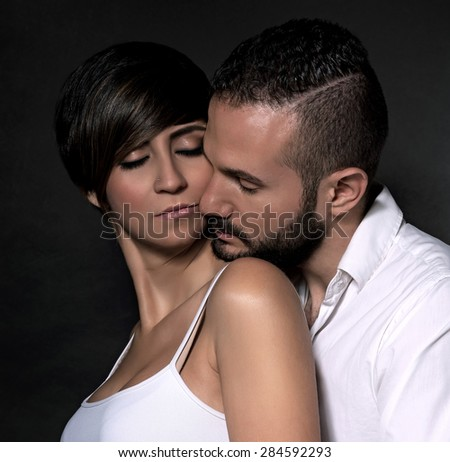 Closeup portrait of beautiful gentle couple in love, hugging with closed eyes of pleasure isolated on black background, romantic relationship - stock photo
