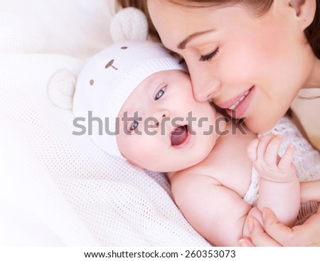 Closeup portrait of beautiful gentle mother playing with cute little baby lying down on the bed, closed eyes of pleasure, loving young family, happy motherhood concept - stock photo