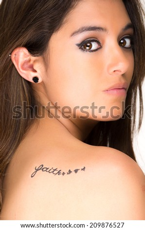 Closeup portrait of beautiful girl with faith tatoo on her back isolated on white - stock photo