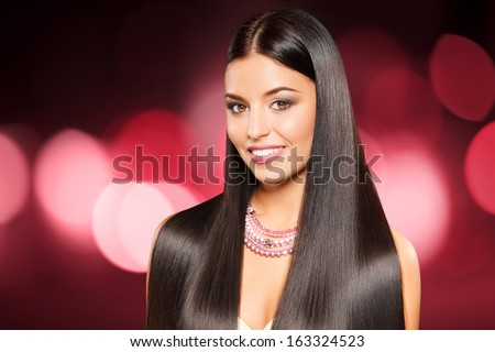 closeup portrait of beautiful girl with straight long dark hair against shining pink background - stock photo