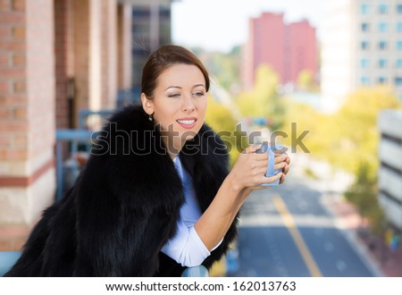 Closeup portrait of beautiful, happy, relaxed woman enjoying a weekend on sunny day, on balcony of her apartment, holding cup of coffee, isolated on city background. Urban life style of businesswoman - stock photo