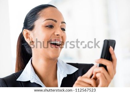 Closeup portrait of beautiful Indian businesswoman sending text message using mobile phone - stock photo