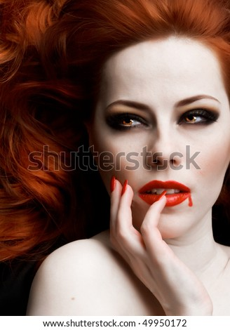 Closeup portrait of beautiful redhead vampire woman - stock photo