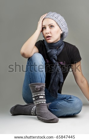 Closeup portrait of beautiful surprised woman sitting comfortably over grey background - stock photo