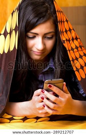 Closeup portrait of beautiful teenage girl using mobil phone hidden under the sheet  in her bedroom - stock photo