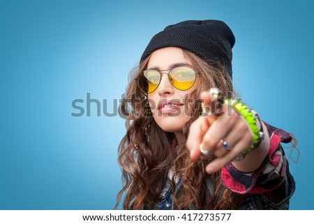 Closeup portrait of beautiful trendy hipster girl with curly hair pointing finger at you and smiling wearing red checkered shirt,denim vest and black beanie hat on blue background.Youth style,fashion. - stock photo