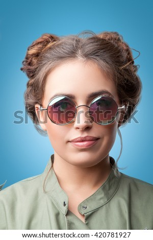 Closeup portrait of beautiful trendy hipster girl with hair buns wearing round sunglasses and green coat  on blue background.Youth style,fashion. - stock photo