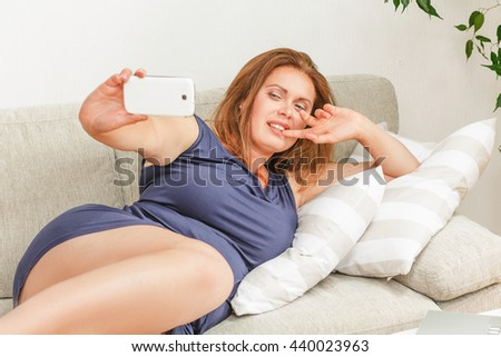 Closeup portrait of beautiful woman making selfie while lying on sofa or couch at home. Red haired lady showing yo sign to camera. - stock photo