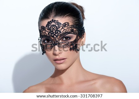 Closeup portrait of beautiful woman with evening smokey makeup and black lace mask over her eyes - stock photo