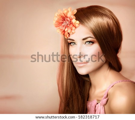 Closeup portrait of beautiful woman with shiny hair and fresh orange flower in it, studio shot, fashion and style, luxury beauty salon - stock photo