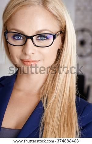 Closeup portrait of beautiful young blonde businesswoman, smiling, looking at camera. - stock photo