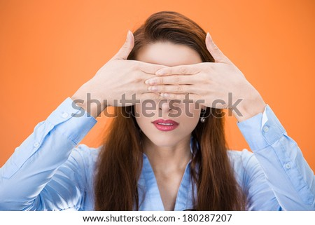 Closeup portrait of beautiful young female, corporate worker, student, citizen closing eyes with hands isolated on orange background. See no evil concept. Human emotions, facial expressions, attitude - stock photo