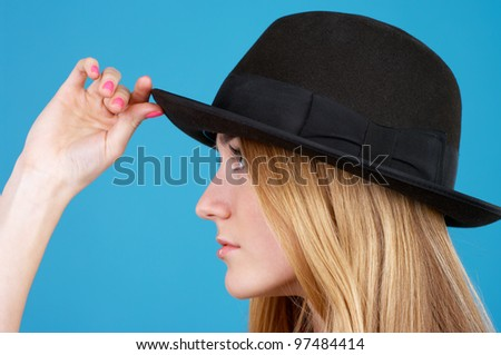 Closeup portrait of beautiful young woman in black hat against blue background - stock photo