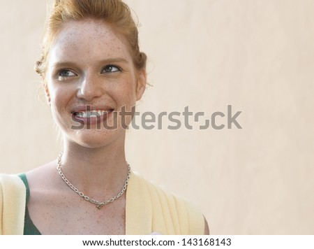Closeup portrait of beautiful young woman smiling outdoors - stock photo