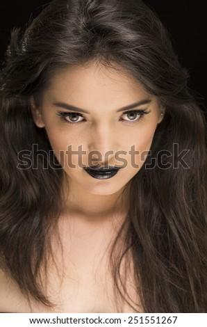 closeup portrait of beautiful young woman wearing goth makeup - stock photo