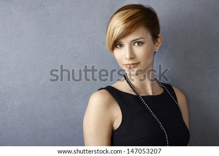 Closeup portrait of beautiful young woman wearing pearl necklace - stock photo