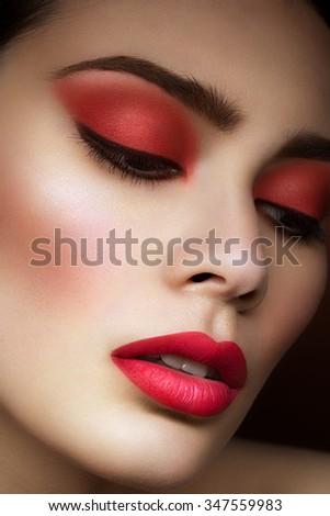 Closeup portrait of beautiful young woman with bright red eyeshadows, lips and nails - stock photo
