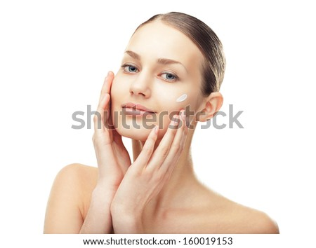 Closeup portrait of  beautiful young woman with cosmetic cream on a cheek isolated on white background - stock photo