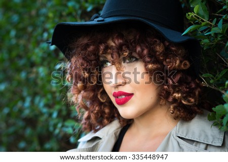 Closeup portrait of beautiful young woman with curly red hair and fedora hat wearing makeup and red lipstick. Beauty portrait of teenage girl with Afro hairstyle Horizontal, retouched. - stock photo