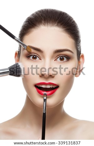 Closeup portrait of beautiful young woman with makeup brushes. Red lips. Happy expression. Isolated over white background. - stock photo
