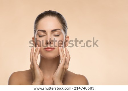 Closeup Portrait of beauty face of beautiful girl with clean and  fresh skin closed eyes  touching her face isolated on beige background with copy place - stock photo