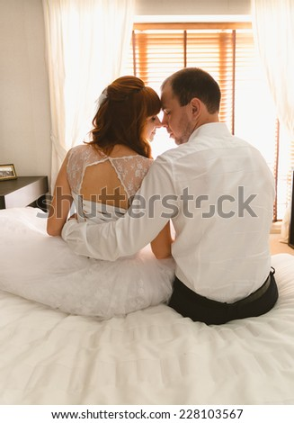 Closeup portrait of bride and groom sitting on bed against big window - stock photo