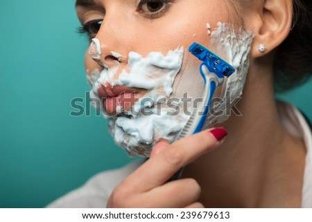 Closeup portrait of brunette shaving her face with foam and razor isolated on blue background. Role gender reversal concept - stock photo