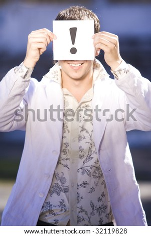 Closeup portrait of businessman holding exclamation mark on boards - stock photo
