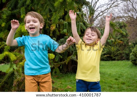 Closeup portrait of Caucasian two little brothers boys laughing outside in park on summer day, backlit with sun from behind, rim light of his figure, selective focus, shallow depth of field Jumping - stock photo