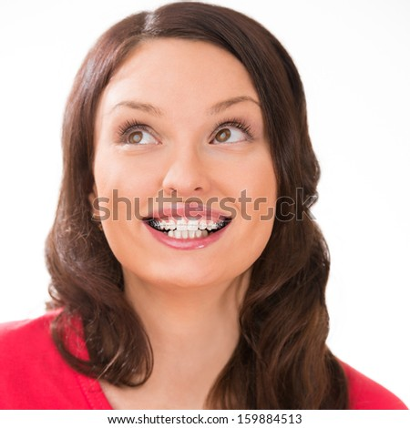 Closeup portrait of charming woman wearing orthodontic braces smiling and thinking about something - stock photo