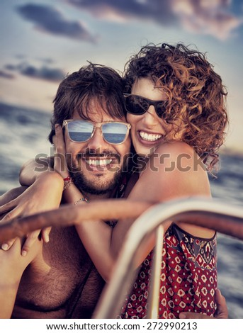 Closeup portrait of cheerful happy lovers on sailboat, young couple having fun in romantic sea traveling, love and enjoyment concept - stock photo