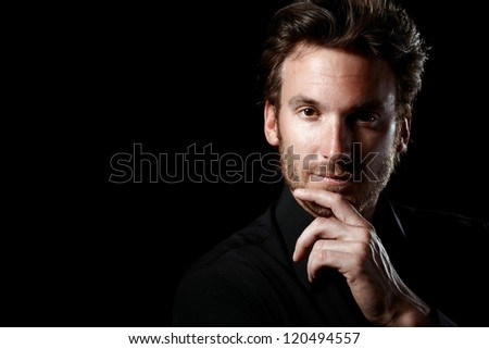 Closeup portrait of confident man thinking, wearing black, looking at camera, black background. - stock photo