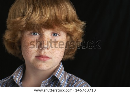 Closeup portrait of confident young boy isolated on black background - stock photo