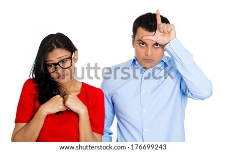 Closeup portrait of couple. Bully husband, man standing  upfront angry, loser sign on head, shy wife, nerdy woman wearing glasses looking downwards, isolated on white background. Human emotion culture - stock photo
