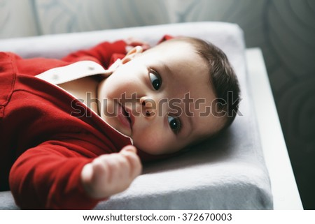 Closeup portrait of cute adorable Caucasian baby boy girl with black brown eyes in red hoodie shirt on changing table looking away from camera, natural light indoors, Instagram filter film effect - stock photo