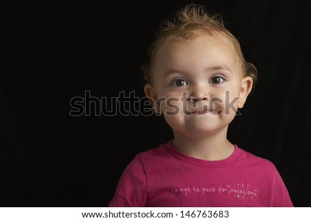 Closeup portrait of cute baby boy against black background - stock photo