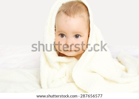 Closeup portrait of cute baby under towel on the bed at home - stock photo
