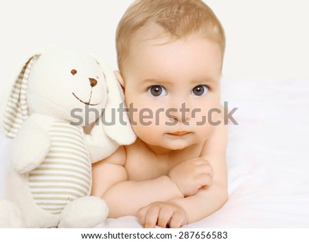 Closeup portrait of cute baby with toy lying on the bed  - stock photo