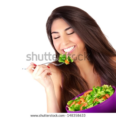 Closeup portrait of cute girl eating salad isolated on white background, enjoying fresh tasty vegetables with closed eyes, healthy lifestyle concept - stock photo
