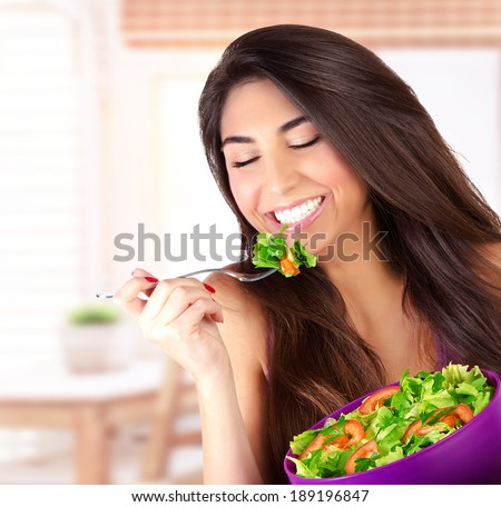 Closeup portrait of cute girl eating salad on the kitchen, enjoying fresh tasty vegetables with closed eyes, healthy lifestyle concept - stock photo