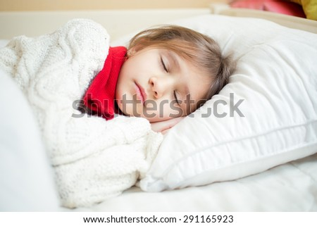 Closeup portrait of cute girl in sweater and scarf lying on white pillow - stock photo