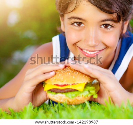 Closeup portrait of cute happy boy eating big tasty fatty burger outdoors, lying down on green field and enjoying sandwich with cheese, meat and vegetables in sunny day  - stock photo
