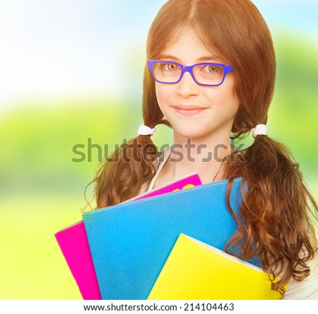 Closeup portrait of cute happy schoolgirl outdoors, wearing glasses, holding in hands different colorful folders, education concept - stock photo
