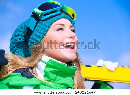 Closeup portrait of cute happy skier girl on blue sky background, extreme winter sport, active lifestyle concept  - stock photo